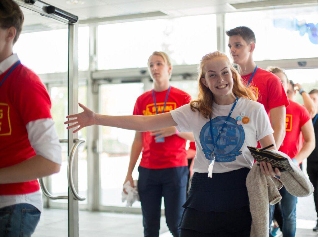 En tjej med en Helsingborg MUF-tröja som entusiastiskt kollar in i kameran med ett leende